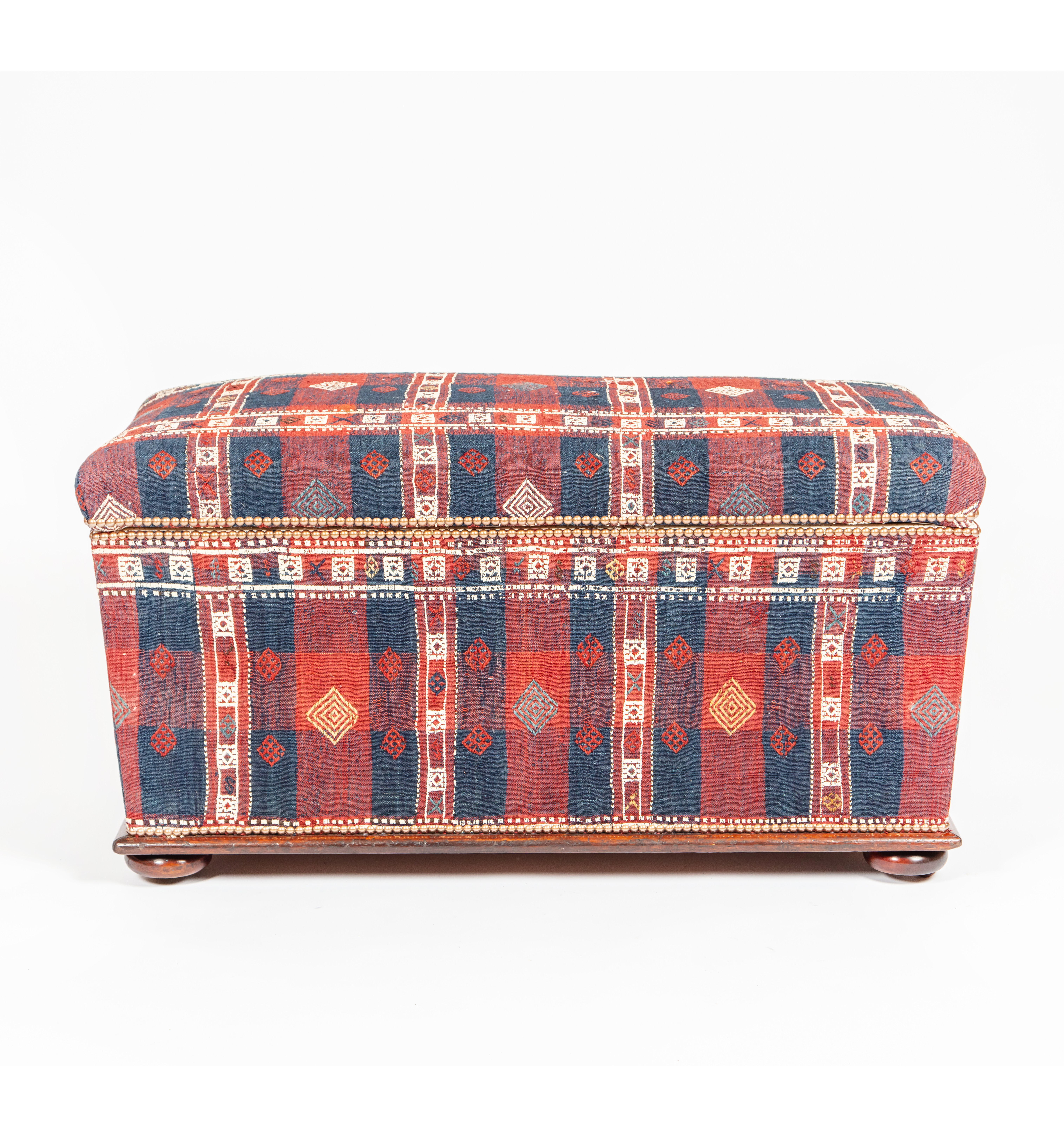 An Ottoman covered in a red and blue checked weave, circa 1880
