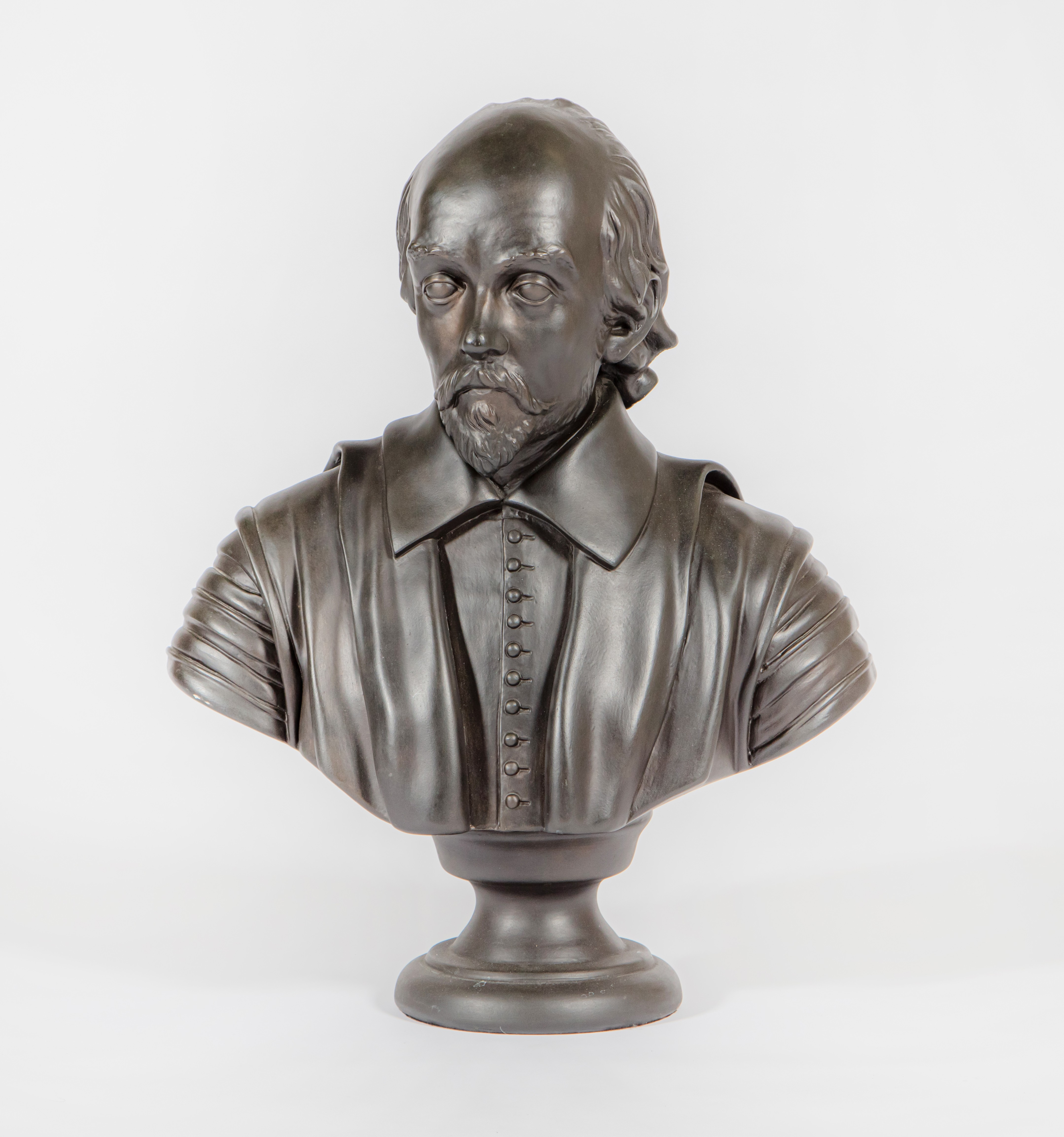 A modern black painted plaster bust of William Shakespeare, raised on a turned socle.