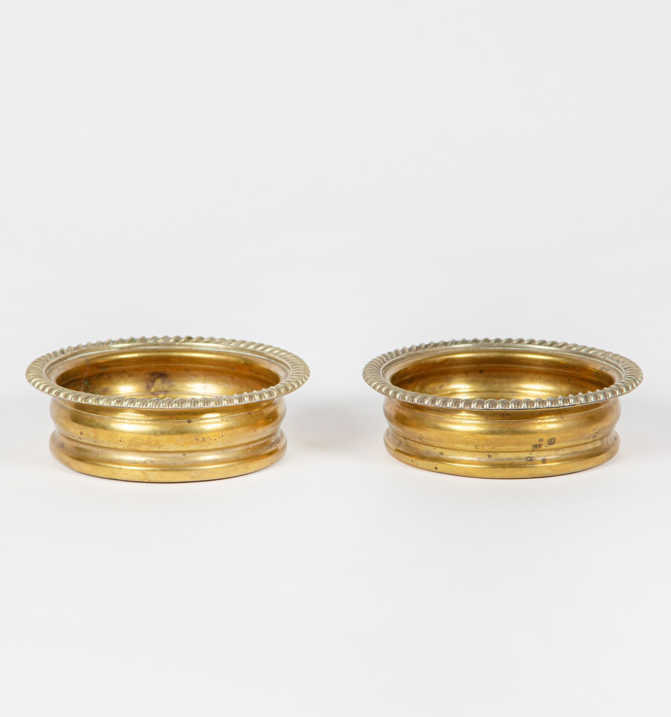 A pair of brass and wooden wine bottle coasters, 19th century